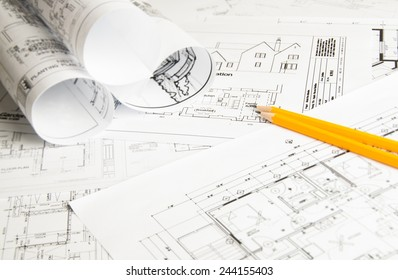Architectural blueprints and blueprint rolls and two yellow pencils