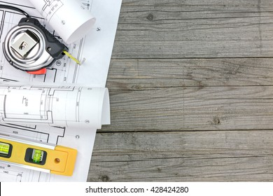 architectural blueprints with spirit level and tape measure on gray wooden boards
