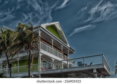 Architectural building Palms in motion hurricane season image retro filtered  Street view of Florida Style residential building against dark sky before tropical hurricane thunderstorm