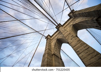 Architectural close-up detail of the landmark Brooklyn Bridge in New York City with its iconic steel cables making criss-cross patterns against a sunset sky