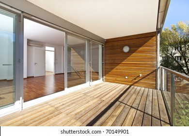architectural contemporary - sunlit balcony with wooden floor and wall of an apartment building in green area.