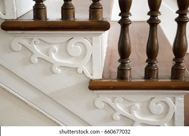 architectural detail of antique stairs with handcrafted scroll-work painted with and turned wood railing.