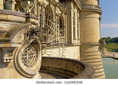Architectural detail   of the castle of chantilly,Oise, France, with ornate fence and sculpture of a man`s head