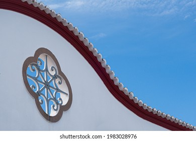 Architectural detail close-up of swooping line rooftop with crenelated edge and rose shaped ornamental window set in whitewashed wall in Tavira Portugal