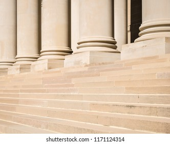 Architectural detail of columns and marble steps outside a government building