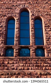 architectural detail of exterior stone wall and stained glass windows
