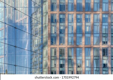 Architectural detail of the facade with multiple reflections of other buildings and the sun in New York