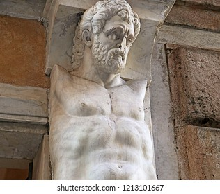 Architectural detail, full size classical man carved torso of white marble supporting the balcony of an antique Renaissance house in Genoa, Italy