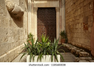 Architectural detail of a large wooden door anchored to two marble columns belonging to a historic building.