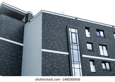 Architectural detail of a modern apartament building. Dark grey brick facde.