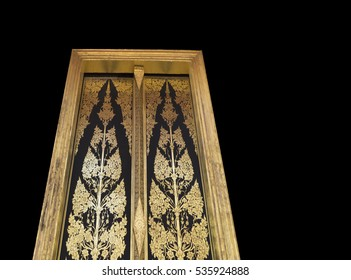 Architectural Detail : Part of Thai Temple Doors Art with Gold and Black Painted Covered with Lacquer  Isolated on Black background