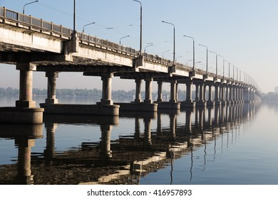 Architectural details and structure   modern concrete bridge in perspective. Reflect on  water surface. Against the background of  city Dnepropetrovsk.
