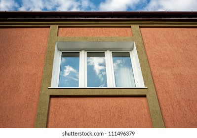 architectural details. window in a building with a brown stucco.