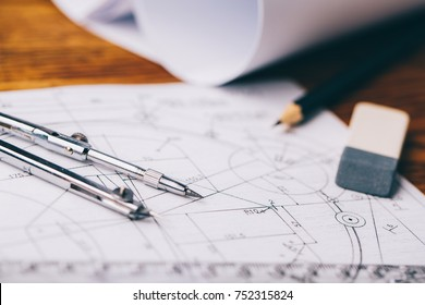 Architectural drawings. Architectural prints and print rolls and a drawing instruments on the worktable. Drawing compass, plans.