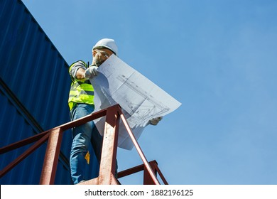 Architectural engineer working on his blueprints in container yard construction site. meeting, discussing,designing, planing, Rear view container ship