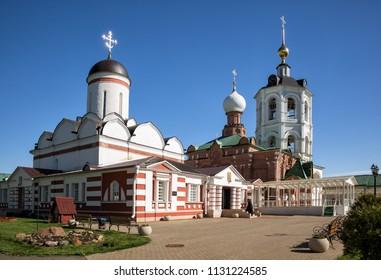 Architectural ensemble of the Nikolo-Peshnoshsky Monastery in Lugovoi. Monk enters temple. Moscow Region, Russia