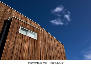 Architectural features of a modern house with wood cladding and a window against a blue sky with a cloud.