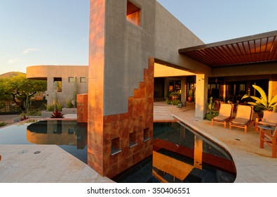Architectural features in pool and patio areas of contemporary luxury home at sunset