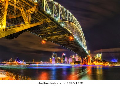 Architectural landmarks of Sydney at dark during light show. Arch of Harbour Bridge above the head towards city CBD and Circular quay behind blurred water in black-white.