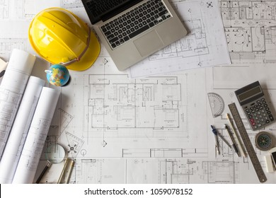 Architectural plan, laptop, dividers ,pencil ,pen ,ruler, glasses and smartphone and blueprint on wooden table. Top view