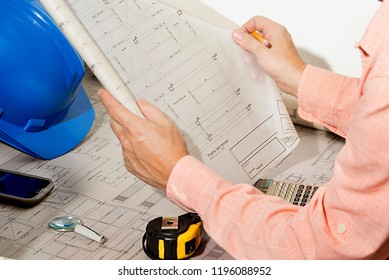 architectural plans of construction- engineer-architect reviewing plans with meter, helmet, calculator and pencil