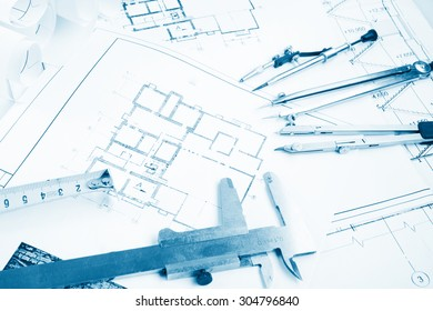 Architectural project, blueprints, blueprint rolls on plans. Engineering tools view from the top. Copy space. Construction background. Blue toned