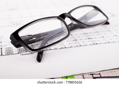 Architectural project and glasses. Construction background.
