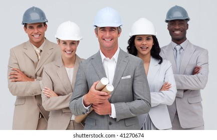 Architectural team smiling at the camera with hard hats and holding blueprints