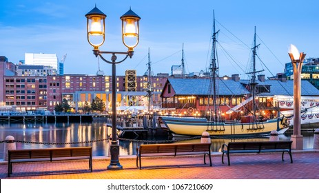 The architecture of Boston in Massachusetts, USA at sunset showcasing the Boston Harbor and Financial District at night.