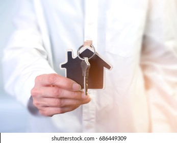 The Architecture, building, house,home,construction, real estate and property concept - close up of hands holding house or home model.Female hand holding house key,real estate agent.