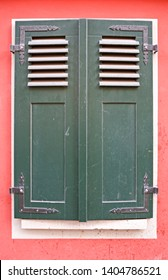 Architecture: Closed green window shutters at a renovated old historical building with a red facade in Eastern Germany