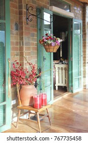 Architecture: Cute Front Door Design, Green Panel, Brick Wall, Flower Vase and Candle.