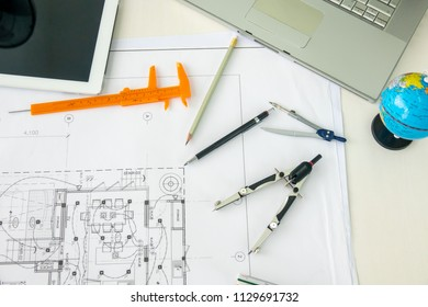 Architecture Desk with equipment architects On the desk with blueprint plan, helmet, wooden house model and tools in the engineering office room. Selective Focus.