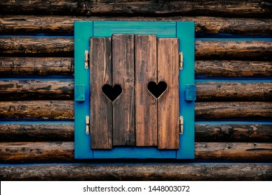 Architecture detail - old wooden window shutters with carved hearts.
