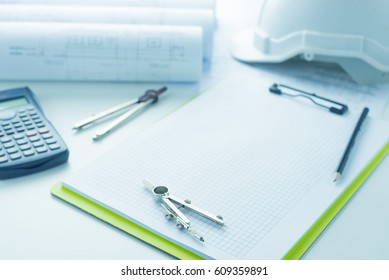Architecture, engineering and construction background concept. Working desk of engineer, Blueprint rolls, Programmable calculator,dividers,clipboard and pencil on white desk.Selective focus.