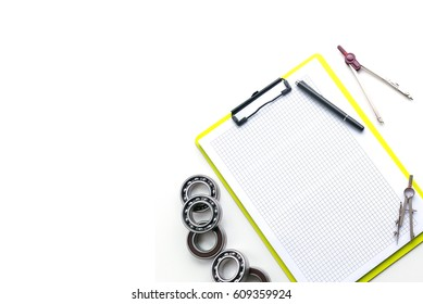 Architecture, engineering and construction background concept. Working desk of engineer, dividers,clipboard, pencil and ball bearing on white desk.Copy space.