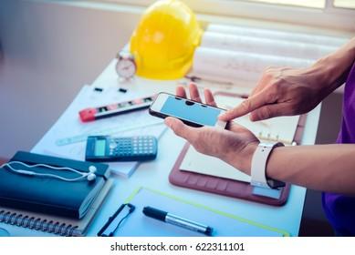 Architecture, engineering and construction background concept. Hand pointing on smartphone,pencil,blueprint rolls,dividers,spirit level and programmable calculator on working desk.