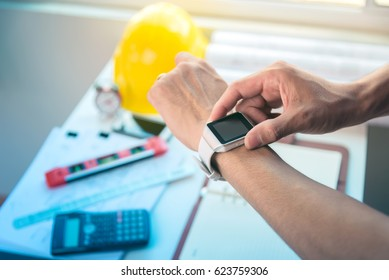 Architecture, engineering and construction background concept. Man using smartwatch.Pencil,blueprint rolls,dividers,spirit level and programmable calculator on working desk.