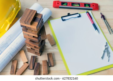 Architecture, engineering and construction background concept.Pen and dividers on clipboard with block wood game,blueprint and spirit level on working desk.