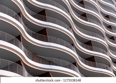 Architecture exterior facade view of modern office building wall with lights and shadows. Modern urban architecture is a wave-shaped building abstract background.