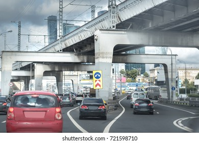 Architecture of highway construction in daytime. Road with cars under the big overpass. Moscow.