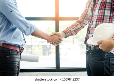 architecture and home renovation concept - builder with blueprint shaking partner hand.