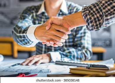 architecture and home renovation concept - builder with blueprint shaking partner hand in retro style.