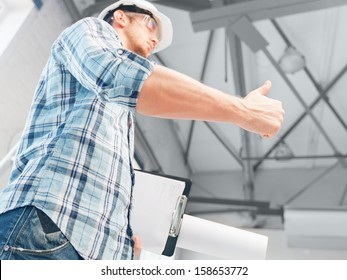 architecture and home renovation concept - man in helmet and gloves with blueprint showing direction