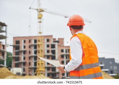 architecture and home renovation concept - man in helmet and gloves with blueprint in factory.