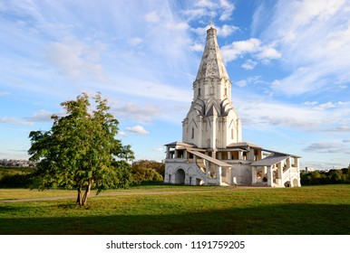 Architecture landmark of The Ascension Church in Kolomenskoye park at sunny autumn day with green tree, lush grass and cloudy blue sky. Famous Moscow place and tourist attraction. Kolomenskoye, Russia