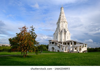 Architecture landmark of The Ascension Church in Kolomenskoye park at sunny summer day with green tree, lush grass and cloudy blue sky. Famous Moscow place and tourist attraction. Kolomenskoye, Russia