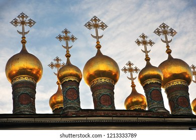 Architecture of Moscow Kremlin. Terem churches. Golden onions are shining in the rays of the sun. Blue sky with clouds background.