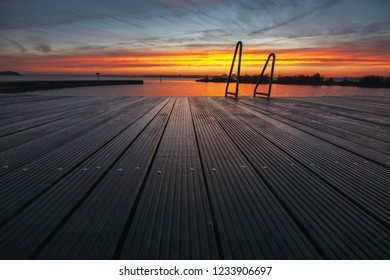 Architecture outdoor swimming pool at the lake with metal aluminum swimming stairs during an impressive intense sunrise.