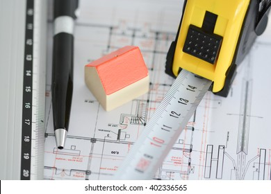 Architecture plans of a building with Small model house on top of blueprints, pen, ruler and notebook